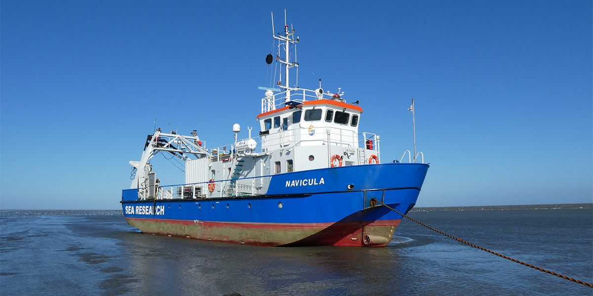 RV Navicula on the mudflats at low tide