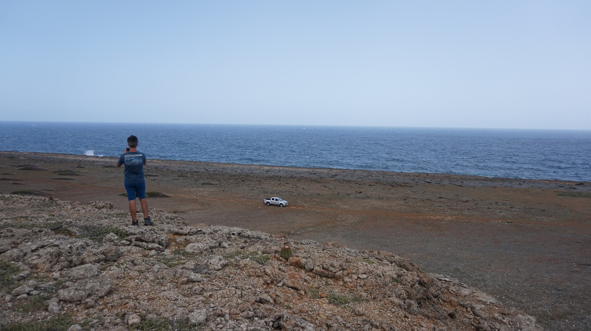 Dr. Alessio Rovere (MARUM,Bremen) is standing on the the edge of the fore reef, where waves used to break.A pick-up car is parked on top of a lower terrace that corresponds to yet another sea-level highstand. Credits: Paolo Stocchi, NIOZ
