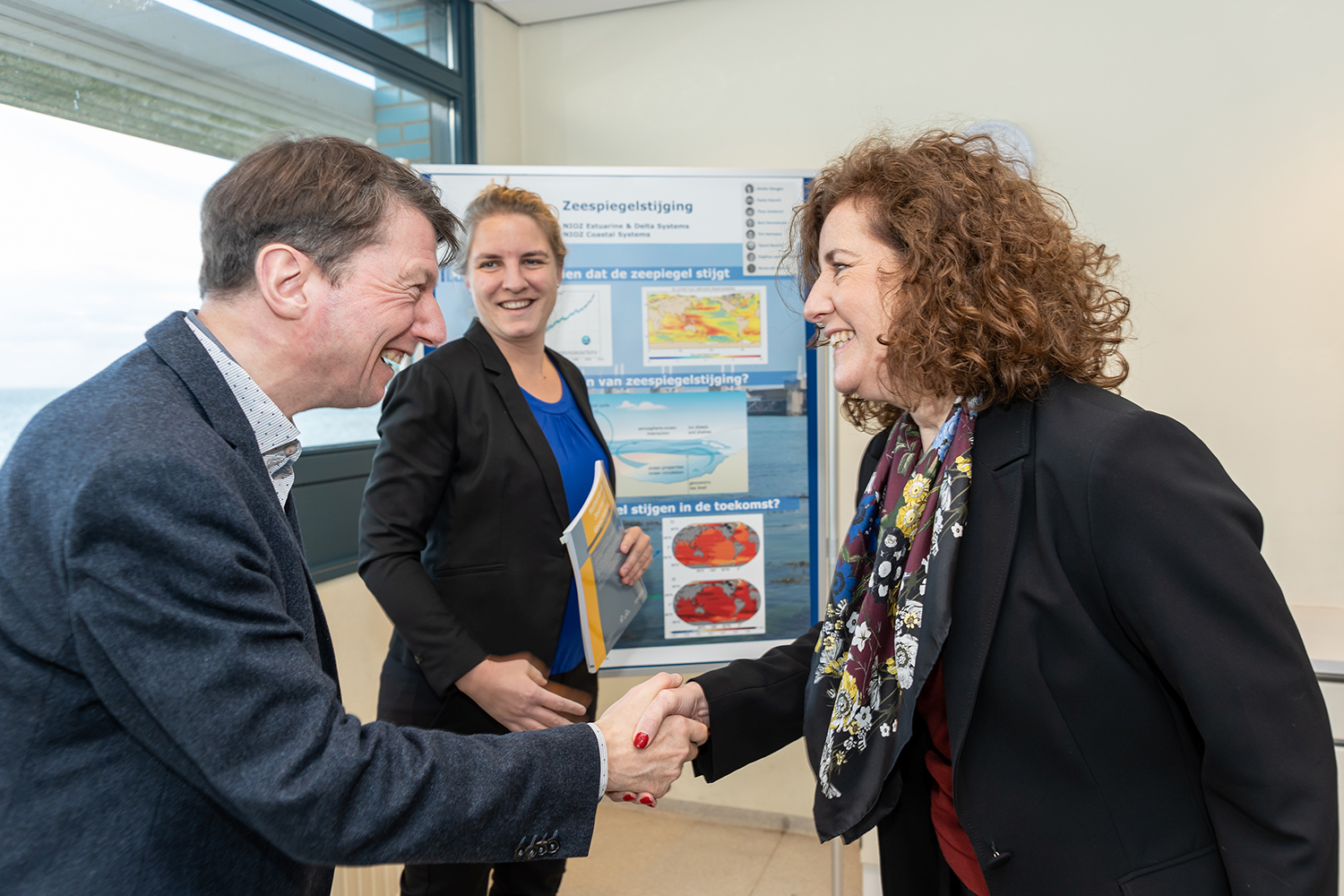 Ingrid van Engelshoven shakes hands with sea level researchers Theo Gerkema and Aimee Slangen.. Foto: Ernesta Verburg.