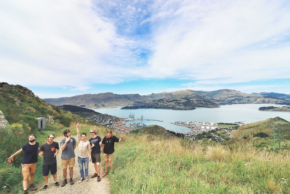 Group photo after hiking up the hills surrounding Lyttelton harbor. For those with keen eyes it is just possible to Spot the orange bow of the R/V Araon.